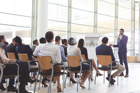 Foto de Front view of handsome mixed-race businessman speaking at business seminar with diverse business people listening to him at conference - Imagen libre de derechos
