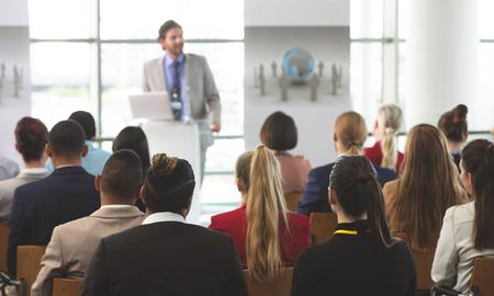 Foto de Rear view of group of diverse business people listening to a Caucasian businessman speak at seminar in modern office - Imagen libre de derechos