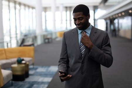 Photo pour Front view of young African-American businessman using mobile phone standing in modern office. He is smiling - image libre de droit