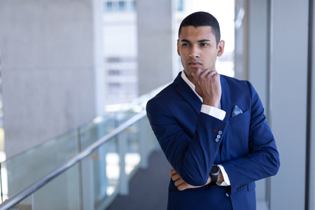 Photo pour Front view of thoughtful young mixed-race businessman with hand on chin looking away standing in modern office - image libre de droit