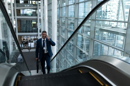 Foto de Front view of Caucasian businessman talking on mobile phone while moving up on escalator in office - Imagen libre de derechos