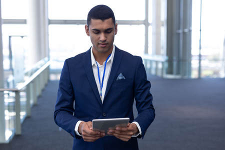 Photo pour Front view of smart young mixed-race businessman using digital tablet standing in modern office - image libre de droit