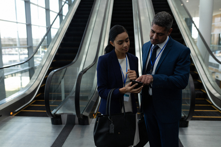 Foto de Front view of mixed-race businessman and businesswoman discussing over mobile phone near escalator in office - Imagen libre de derechos