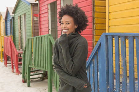 Front view of pretty happy young African American woman standing at beach hut. She is smiling