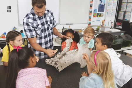 Photo for Front view of a teacher explaining and showing animal skeleton to his pupils in classroom - Royalty Free Image
