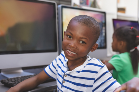Photo pour Portrait of happy African-american schoolboy sitting and looking at camerain computer room - image libre de droit