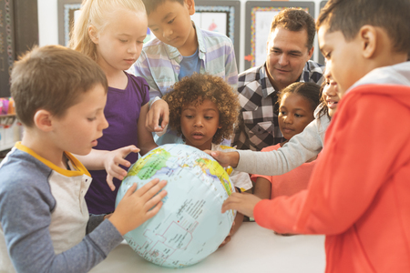 Photo for Front view of a schoolteacher discusing over a earth globe in classroom at school with his school kids - Royalty Free Image
