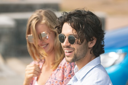 Foto de Side view of happy young Caucasian couple with sun glasses standing on beach promenade on a sunny day. They are smiling - Imagen libre de derechos