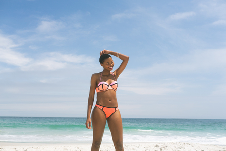 Front view of African-american woman posing while standing on beach on a sunny day