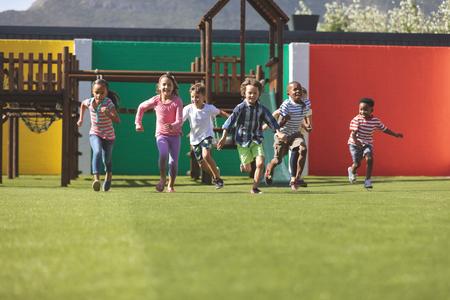 Foto de Front view of multi ethnic students running in school playground - Imagen libre de derechos