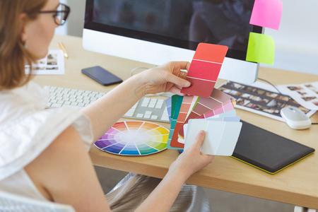 Foto de High angle view of young Caucasian graphic designer checks the color with color swatch at desk in office - Imagen libre de derechos