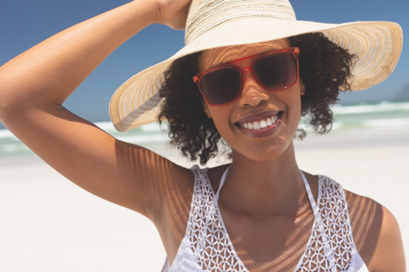 Photo pour Portrait of beautiful young mixed-race woman smiling and looking at camera standing at beach on a sunny day. She wears hat and red sunglasses - image libre de droit