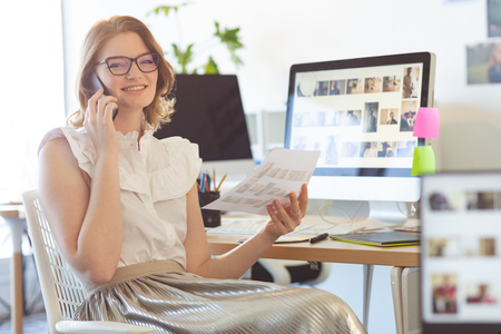 Photo pour Portrait of young Caucasian female graphic designer talking on mobile phone in office. She is smiling and looking at camera - image libre de droit