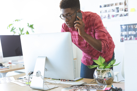 Foto de Side view of young African-American graphic designer talking on mobile phone while working on computer at desk in office - Imagen libre de derechos
