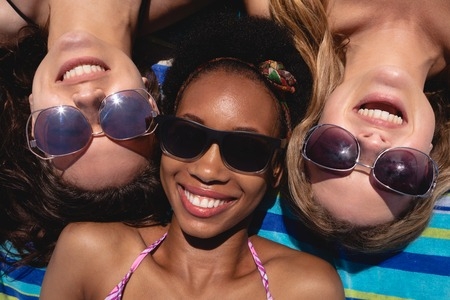 Photo pour Close-up of happy beautiful young multi ethnic women with sunglasses lying on beach in the sunshine - image libre de droit