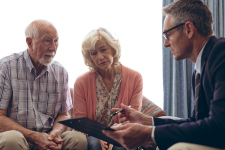 Foto de Side view of matured Caucasian male physician interacting and showing papers to senior Caucasian couple at retirement home - Imagen libre de derechos