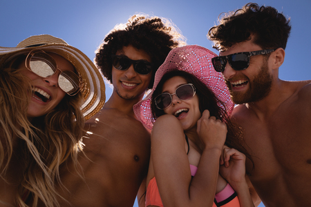 Photo for Low angle view of happy group of Multi ethnic friends having fun at beach in the sunshine against blue sky - Royalty Free Image