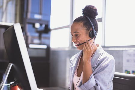 Photo pour Side view of young mixed-race businesswoman talking on headset while working on computer at desk in the office - image libre de droit