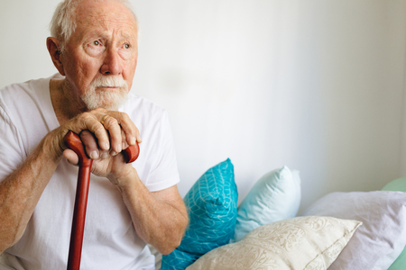 Front view of senior Caucasian male patient sitting upset on bed with stick at retirement home