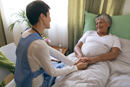 Photo pour Front view of Asian female nurse taking care of senior mixed race  female patient at retirement home. Senior female is lying in bed. - image libre de droit