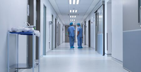 Photo pour Rear view of diverse surgeons talking with each other in the corridor at hospital - image libre de droit
