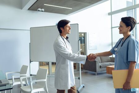 Photo pour Side view of male happy Caucasian doctor shaking hands with smiling female Caucasian nurse in the hospital - image libre de droit