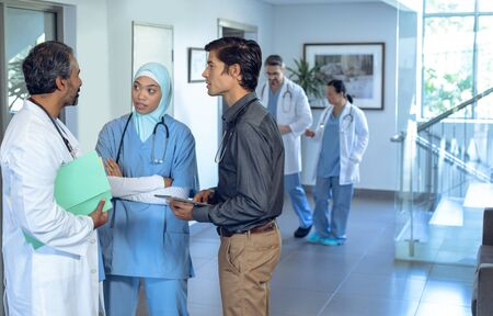 Foto de Side view of diverse medical team of doctors talking with each other in lobby at hospital. In the background colleagues are discussing in the hallways. - Imagen libre de derechos