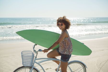 Photo pour Front view of beautiful African american woman holding a surfboard with bicycle at beach - image libre de droit