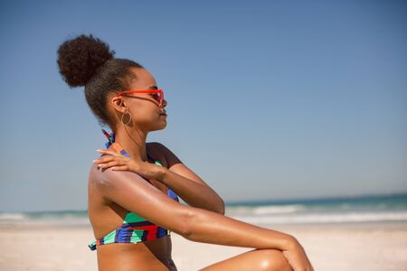 Photo pour Side view of African american woman in bikini applying sunscreen lotion on shoulder at beach in the sunshine - image libre de droit