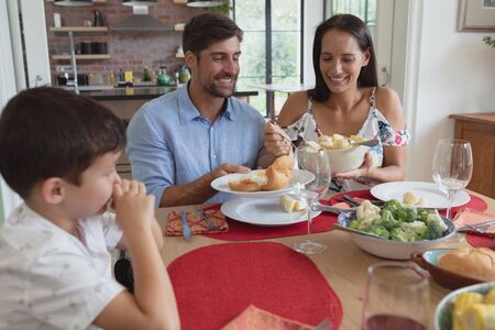 Photo pour Front view of happy Caucasian family having food at dinning table in a comfortable home - image libre de droit