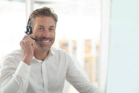 Photo pour Front view of Caucasian male customer service executive talking on headset at desk in a modern office - image libre de droit