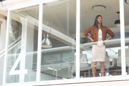 Photo pour Front view of happy mixed race businesswoman with hands on hips standing near window in a modern office - image libre de droit