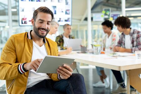 Photo pour Front view of Caucasian male fashion designer using digital tablet while diverse business people discussing in the conference room at office - image libre de droit