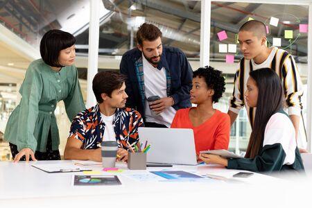Foto de Front view of diverse business people discussing over laptop in the conference room at office - Imagen libre de derechos