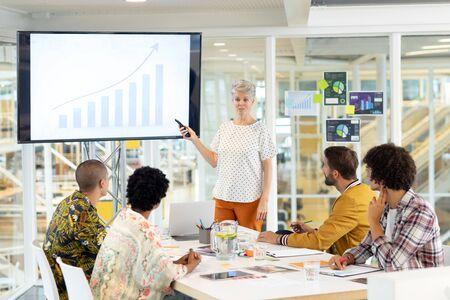Foto de Front view of mature Caucasian businesswoman giving presentation on screen during meeting in a modern office - Imagen libre de derechos