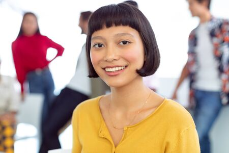 Photo pour Front view of happy young Asian businesswoman looking at camera in a modern office - image libre de droit