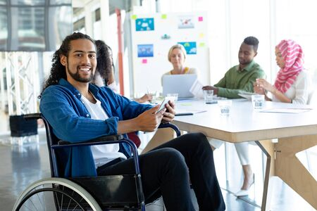 Photo pour Front view of Mixed-race disabled businessman with digital tablet looking at camera in conference room during meeting in a modern office - image libre de droit