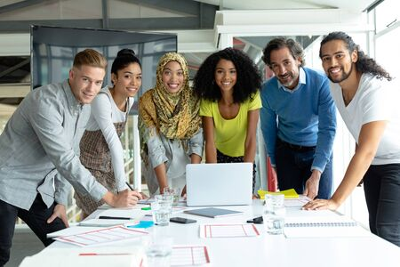Foto de Front view of diverse business people looking at camera while working together at conference room in a modern office - Imagen libre de derechos