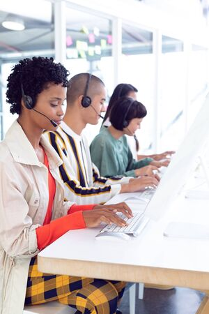Photo for Side view of diverse customer service executives working on computer at desk in office - Royalty Free Image