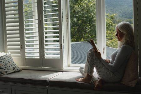 Photo pour Side view of active senior Caucasian woman reading a book on window seat at home - image libre de droit