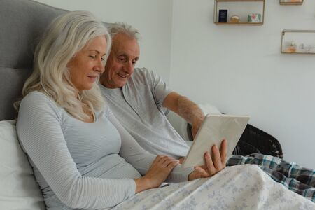 Photo for Side view of active senior Caucasian couple using digital tablet in bedroom at home - Royalty Free Image