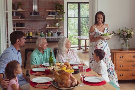 Photo pour Front view of happy Multi-generation Caucasian family having food on dining table at home - image libre de droit