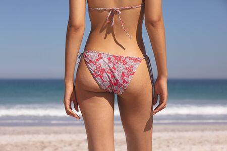 Photo pour Mid section of mixed race woman in bikini standing on the beach - image libre de droit