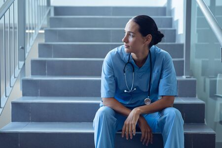 Foto de Front view of thoughtful mixed race female doctor sitting on staircase in the hospital - Imagen libre de derechos