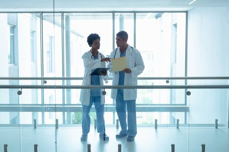 Photo pour Front view of diverse male and female doctors interacting with each other in the corridor at hospital - image libre de droit