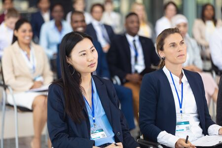 Photo pour Front view of diverse business people sitting on chairs while listening to speech in conference room - image libre de droit
