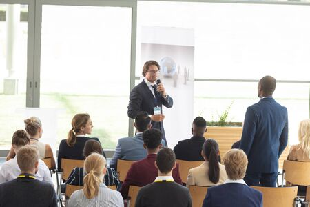 Photo pour Rear view of young African-american male executive asking question during conference - image libre de droit
