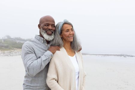 Front view of happy senior African-American couple standing on the beach on cloudy day. Authentic Senior Retired Life Concept