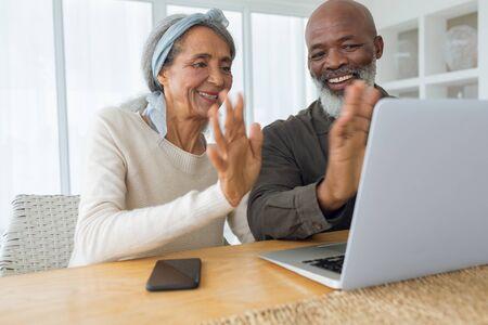 Foto de Front view of diverse senior couple video chatting using laptop in beach house. They are waving. Authentic Senior Retired Life Concept - Imagen libre de derechos