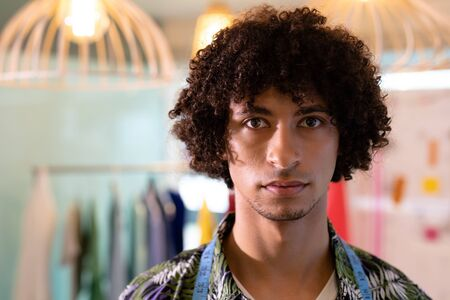 Portrait of young mixed race male fashion designer standing in design studio. This is a casual creative start-up business office for a diverse team